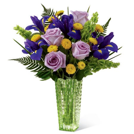 Lavender roses, purple iris, yellow button poms, Bells of Ireland and sword fern create a truly stunning and unique flower arrangement
