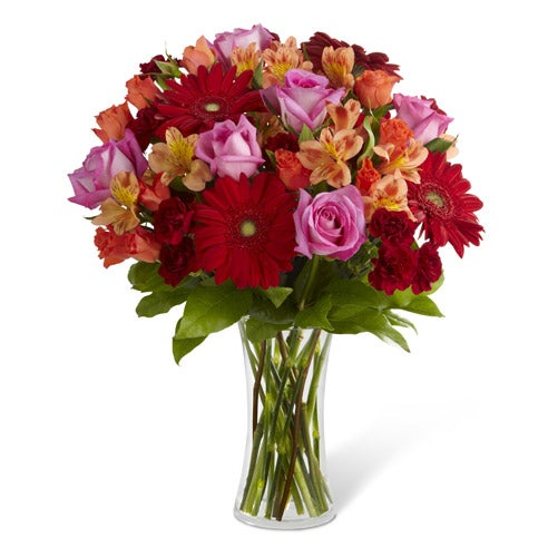 Dawning Love bouquet: red gerbera daisies, hot pink roses, orange spray roses, burgundy mini carnations, and peach peruvian lilies