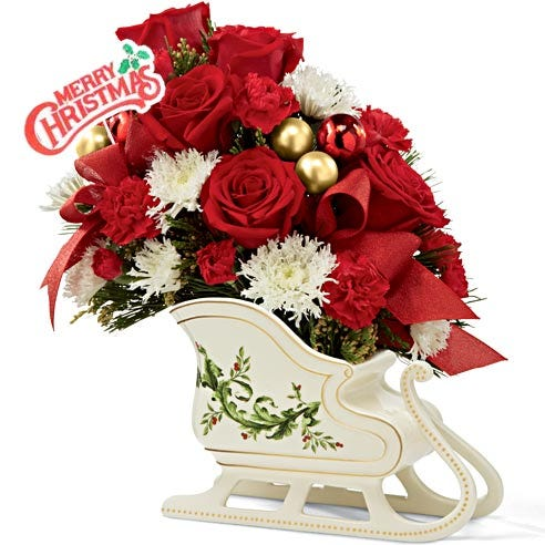 Red roses and white flowers arranged in a sleigh for a christmas gift