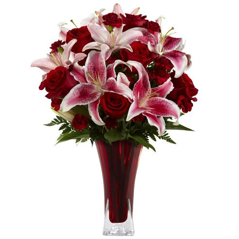 Red stargazer lily red roses and red carnations bouquet in a red glass vase