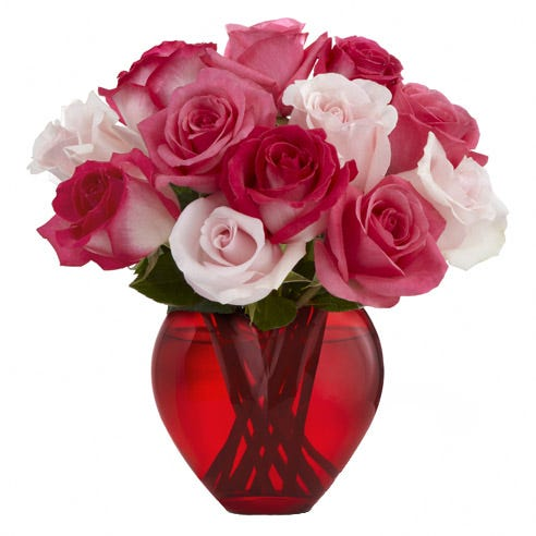 Heart shaped mixed fuchsia and pink roses bouquet in a red glass vase