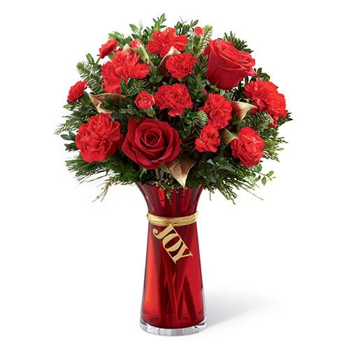 red roses and red carnations in a red glass vase that says Joy