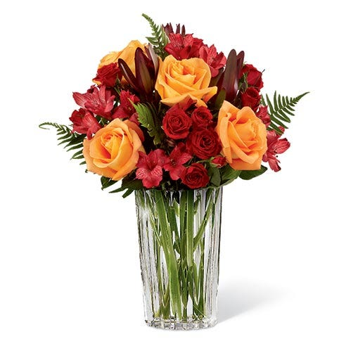Orange rose and red Peruvian lilies with red spray roses in a crystal vase