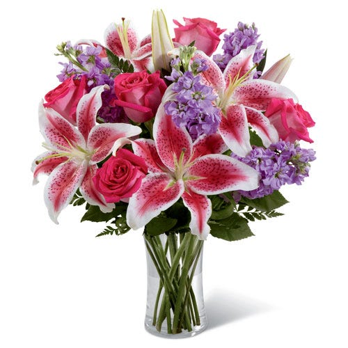 Hot pink roses and stargazer lily bouquet inside a glass purple vase