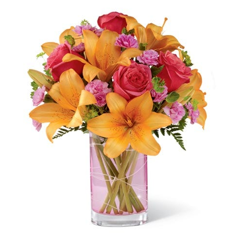 Floral arrangement in vibrant colors: peach roses, orange lilies, pink mini carnations in a pink hand-etched vase