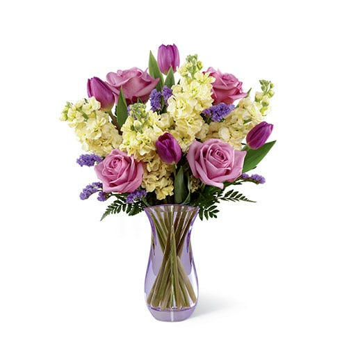 Lavender roses, purple tulips, purple statice, pale yellow stock, and lush greens