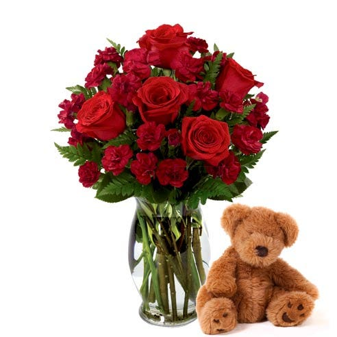 Red roses bouquet hand delivered with a teddy bear and clear glass vase