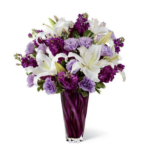 Lavender double lisianthus and ivory oriental lily bouquet in a dark purple vase