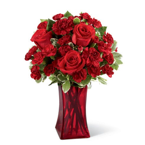Red roses and red mini carnations in a red glass vase