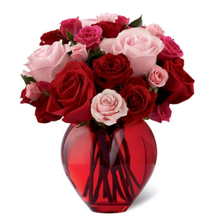 Cheap flowers in a mixed red rose bouquet in a red glass vase for cheap rose delivery