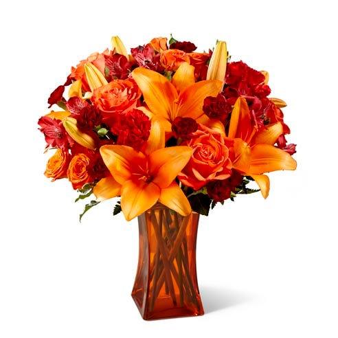 Dark orange roses and orange lilies bouquet inside a clear orange vase