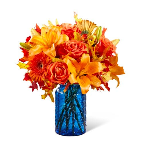 orange and blue flower bouquet with orange lilies, roses, and gerbera daisies in blue vase