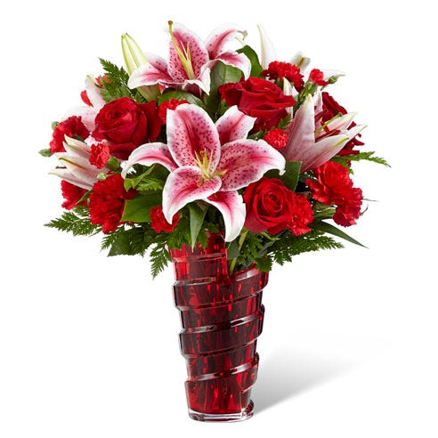 Red stargazer lilies, red roses and green filler in a red vase
