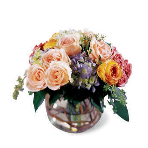 Peach roses, purple hydrangea and mixed flowers in a circle vase