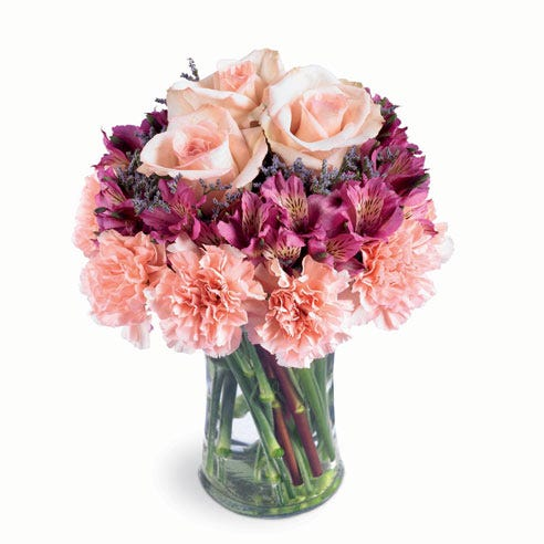 Pink carnations and lavender alstroemeria in a glass vase