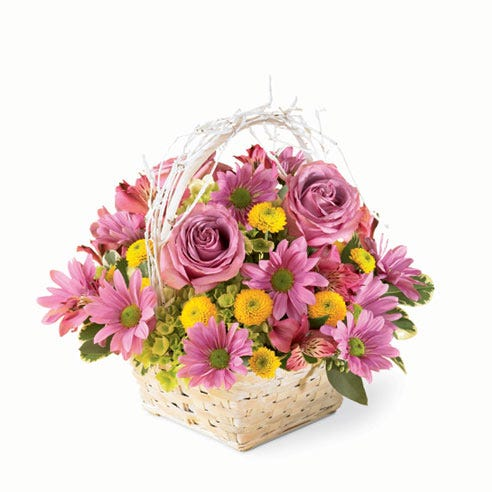 Purple roses, purple carnations and yellow button poms in a white basket