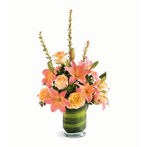 Orange lilies are arranged with lilies and ti leaves