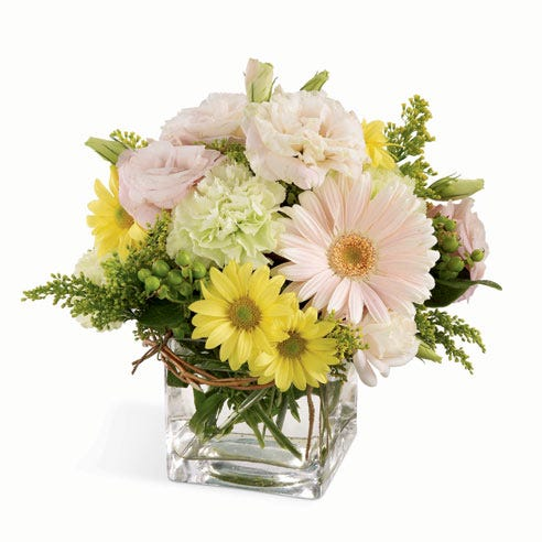 Pink gerbera daisies with yellow daisies and green carnations in a square vase