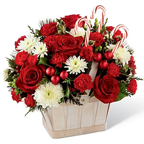 Red and white flowers delivered in a basket with mini ornaments and candy cane