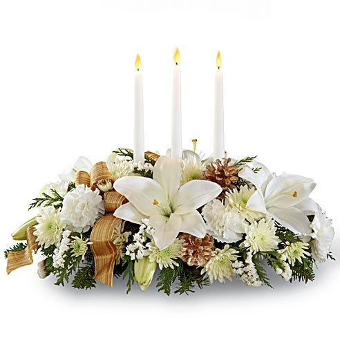 Holiday centerpiece with white lilies and christmas flowers in a candle centerpiece delivery