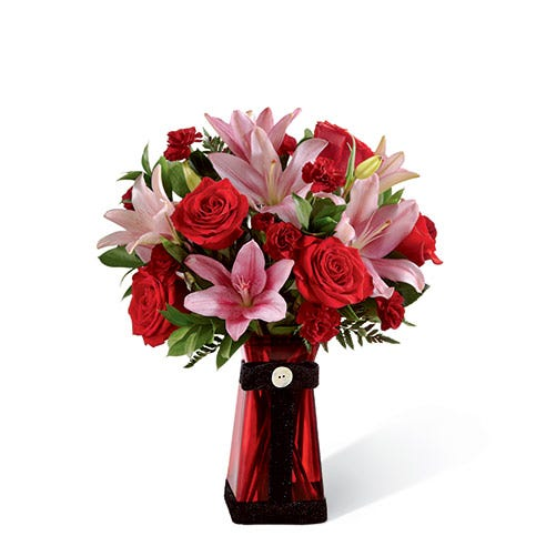 Long stem red roses, red mini carnations and pink lilies in a red vase