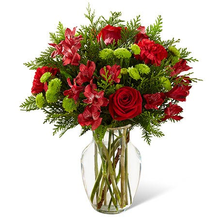 Christmas flower bouquet with red carnations, alstroemeria, evergreen stems and glass vase