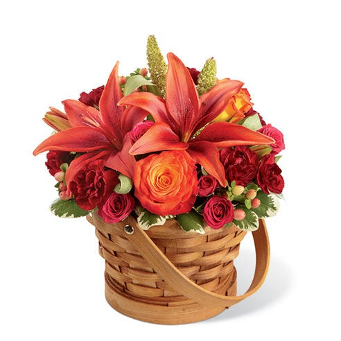 Orange lilies, bi-colored orange roses and mini red carnations in a woven basket