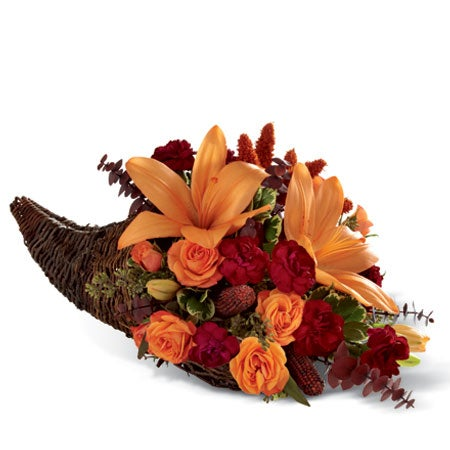 Thanksgiving flowers bouquet with orange lilies inside a cornucopia