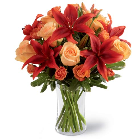 Red lilies delivered with orange spray roses in a glass vase