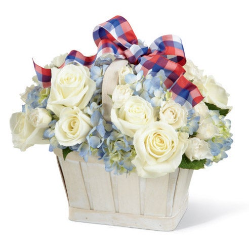 White roses, white spray roses and blue hydrangea in a white basket with colorful ribbon