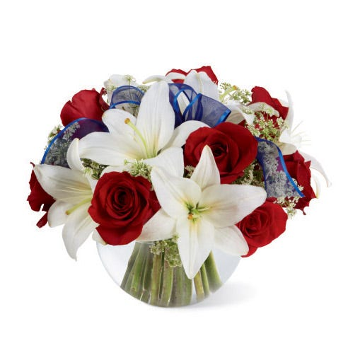 White lilies, red roses and a blue ribbon in a vase