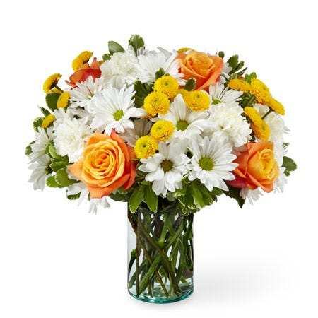 Orange rose white daisy and yellow button pom flower bouquet in a clear vase