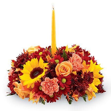 Fall floral centerpiece with sunflowers, orange roses and carnations and yellow candle