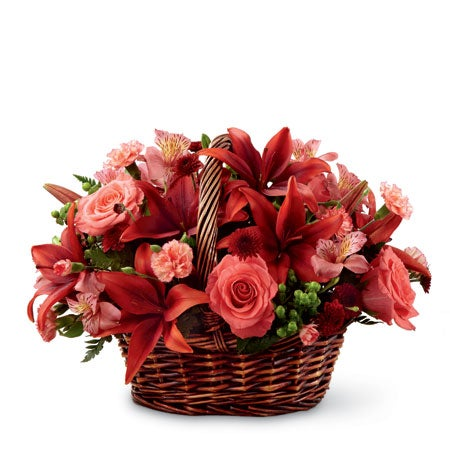 Orange roses and red lilies in a basket of flowers