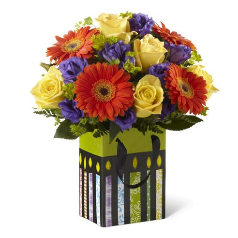Yellow roses, orange daisies and purple flowers in birthday present vase