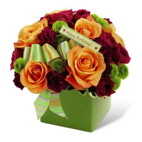 Orange roses, green button pompons and hot pink spray roses in unique green vase