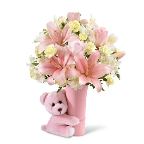 Pastel pink roses, pale yellow mini carnations, white Peruvian lilies, pink Asiatic lilies and a variety of greens in a blushing pink ceramic vase hugged by a pink plush bear