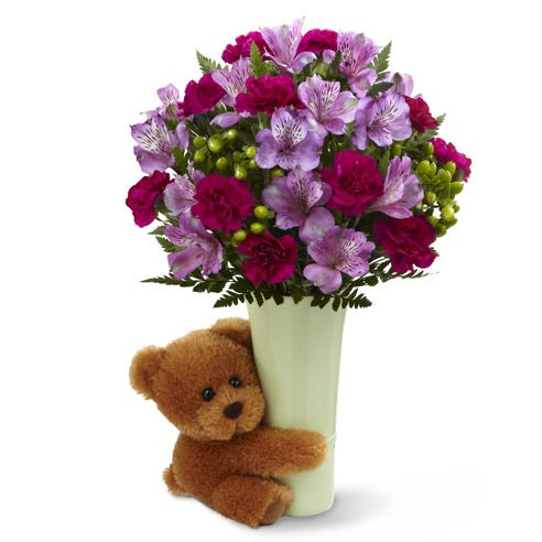 Purple alstroemeria and purple carnations in a vase wrapped by a teddy bear