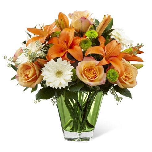 Peach roses, white gerbera daisies, green button poms in a glass vase