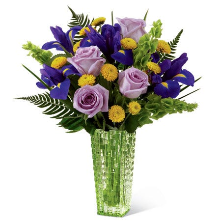 Purple roses in a green glass vase