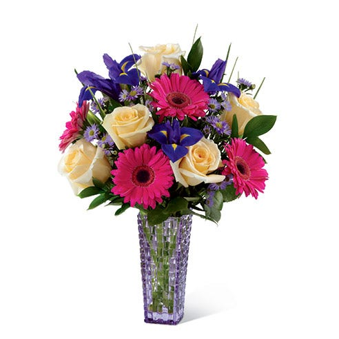 Yellow roses, hot pink gerbera daisies and purple iris in a purple vase