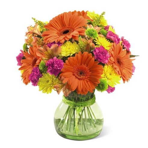 Orange gerbera daisies, yellow poms and pink carnations in green vase