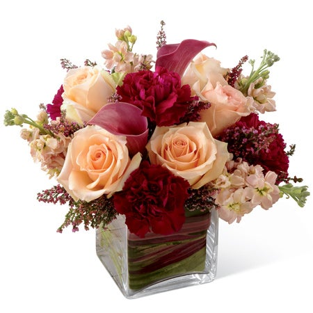 Peach roses, burgundy mini carnations, plum mini calla lilies, and peach stock in a clear glass cubed vase
