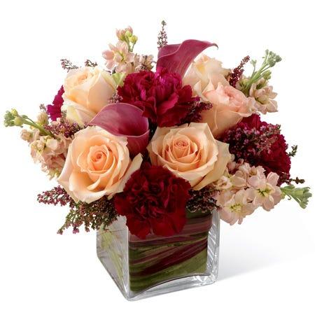 Peach roses, burgundy mini carnations, plum mini calla lilies, and peach stock in a clear glass cubed vase