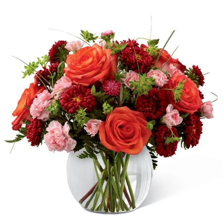 Red matsumoto asters, light pink mini carnations & greens in a circular vase