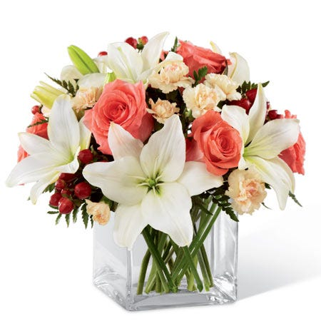 Coral roses, white Asiatic lilies, peach mini carnations, and red hypericum berries in a clear glass cube vase