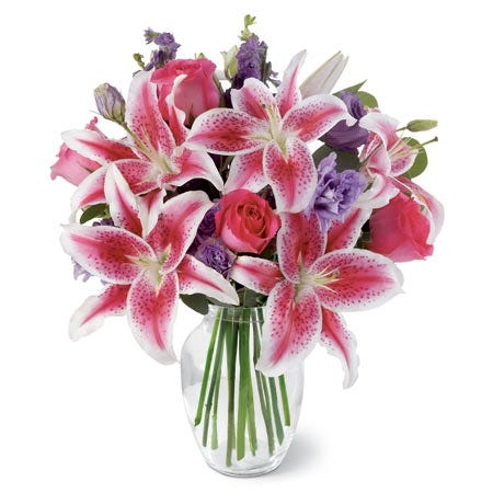 Hot pink roses, pink stargazer lilies, purple lisianthus, larkspur, and silver dollar eucalyptus in a glass vase