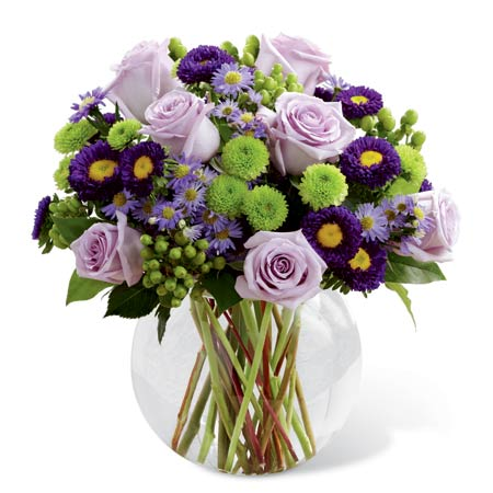 Purple roses spring flowers centerpiece in bowl and purple flower centerpiece