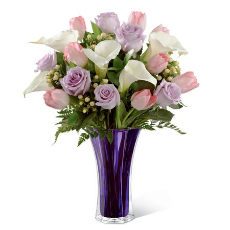 White open-cute calla lilies, pale pink tulips, lavender roses, and peach hypericum berries housed in a keepsake violet flared glass vase