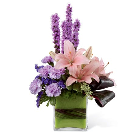 Pink Asiatic lilies, lavender carnations, purple liatris, and purple statice in a glass cubed vase